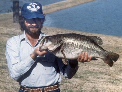 Colored photo with man wearing a blue hat, blue button up shirt, lake in background, and holding the largest largemouth bass every caught in Texas.